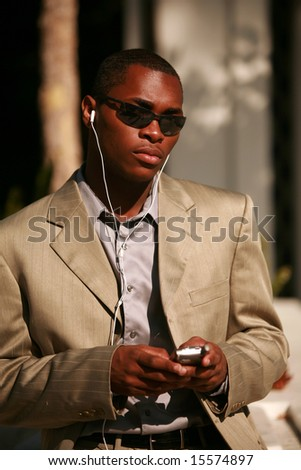 a well dressed business man text messages on his cell phone outside while listening on his personal digital music player