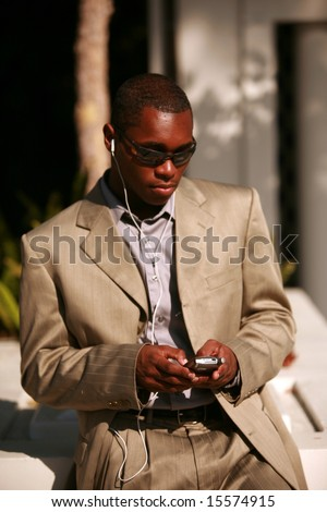 a well dressed business man text messages on his cell phone outside while listening on his personal digital music player - stock photo