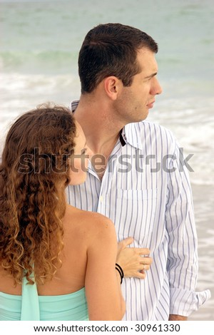 A well dressed young couple facing each other, looking to the right, the ocean is in the background - stock photo