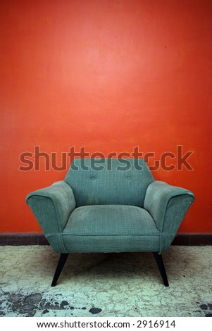 A well worn chair set against an orange wall in a room in Mexico. - stock photo