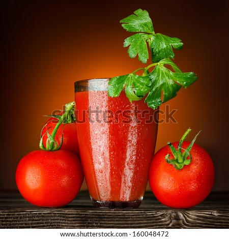 A wet glass of tomato juice decorated with parsley and ripe tomato bunch on a wooden table. - stock photo