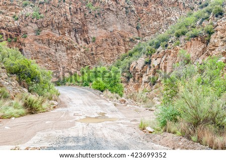 A wet Nuwekloofpas (new valley pass) crossing a small river while descending into the Baviaanskloof (baboon valley) during a rain storm - stock photo