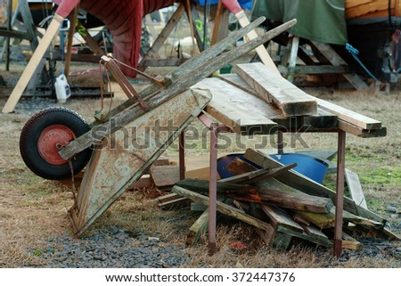 A wheelbarrow is resting against a makeshift worktable in a marina. Boat keels in background, Wooden planks at tabletop and debris underneath.  - stock photo