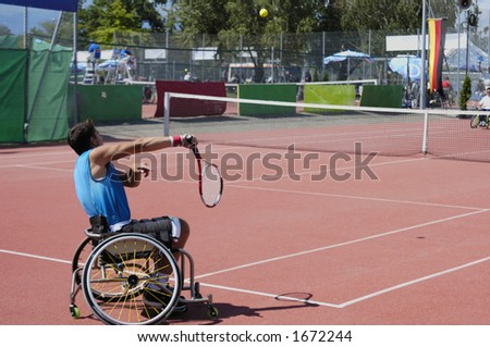 A wheelchair tennis player during a tennis championship match, serving. The ball, with motion blur, is visible centre top. - stock photo