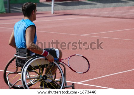 A wheelchair tennis player during a tennis championship match, waiting to take a shot. Space for text. - stock photo