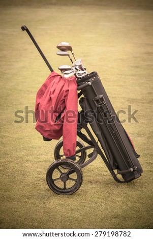 a wheeled golf bag full of golf clubs of a vibrant golf course - stock photo