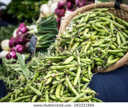A whicker basket of fava beans at a San Francisco farmer's market.  Onions and other vegetables on a table in the background. - stock photo