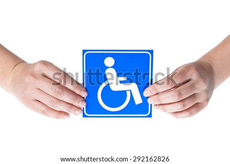 A white and blue symbol of disabled people held in both female hands on a white background - stock photo