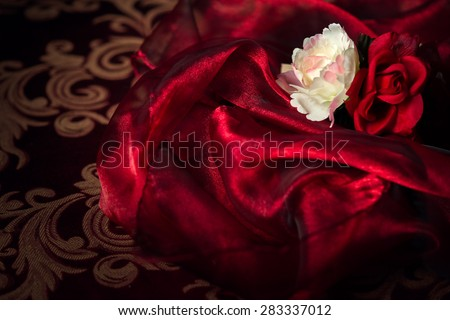 A white and red silk rose and carnation sits atop a wadding of luxurious, flowing silk material.