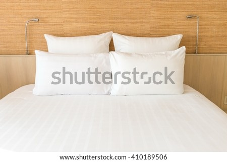 A white bed with 4 pillows and 2 head lights - stock photo