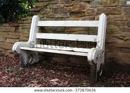 A white bench in a restful garden against a stone wall. - stock photo