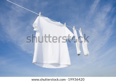A white blank t-shirt hanging on a clothesline in front of a blue sky background with copy space - stock photo