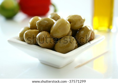 A white bowl containing fresh green olives - stock photo
