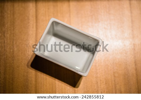 A white bowl on wooden floor - stock photo