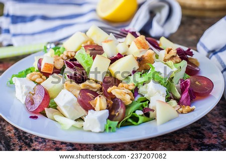 a white bowl with fresh fruit and lettuce greek salad with feta cheese - stock photo