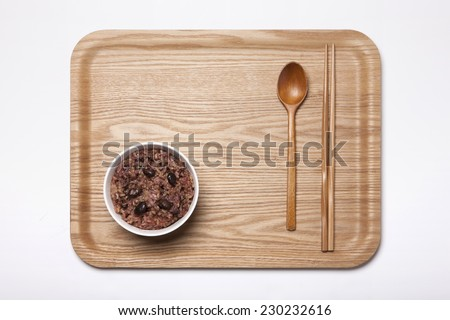A white bowl with multi-grain rice and wood tray, chopstick, spoon isolated white top view at the studio. - stock photo