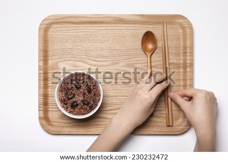 A white bowl with multi-grain rice and wood tray, female hand, chopstick, spoon isolated white top view at the studio. - stock photo