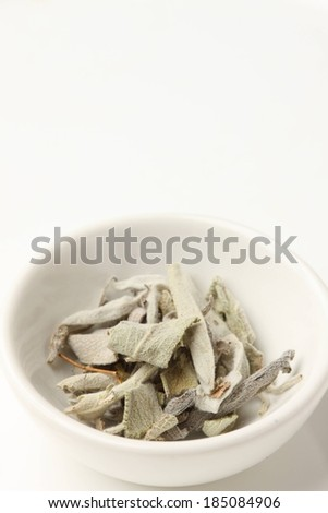 A white bowl with some dry herb leaves in it. - stock photo