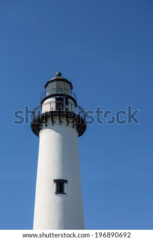 A white brick lighthouse with black iron hardware on a clear blue sky