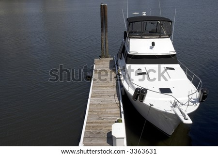 A white cabin cruiser berthed next to a small wooden jetty. - stock photo