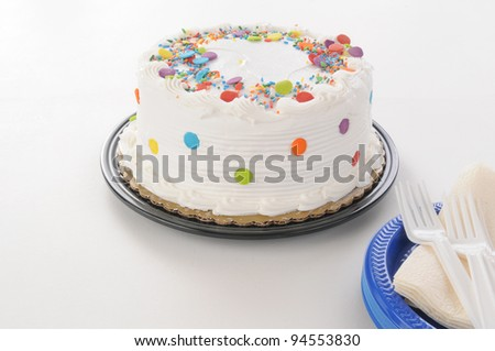 A white cake with candy sprinkles and plastic plates - stock photo
