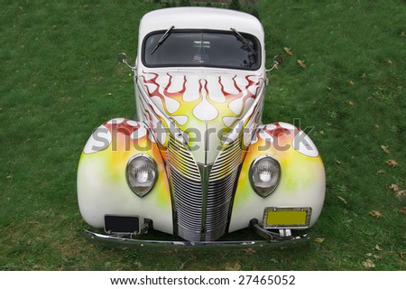 A white car with a flame design on the front sitting on grass. - stock photo
