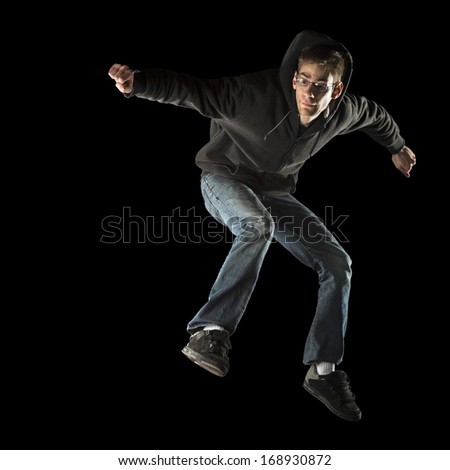 A white Caucasian man jumps with casual urban fashionable clothing on. Isolated on a black background. - stock photo