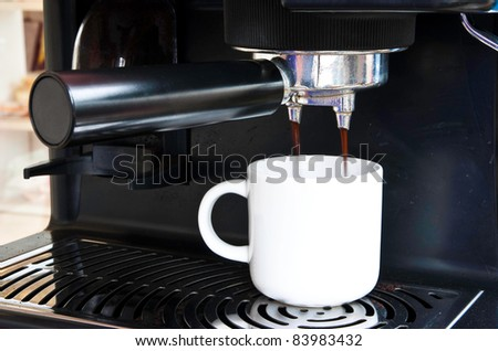 A white ceramic cup of freshly brewed strong coffee pouring from coffee machine - stock photo