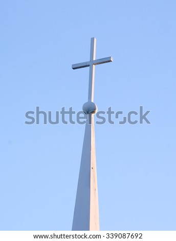 A white church cross sits atop a rural church, cast against the blue sky above. - stock photo