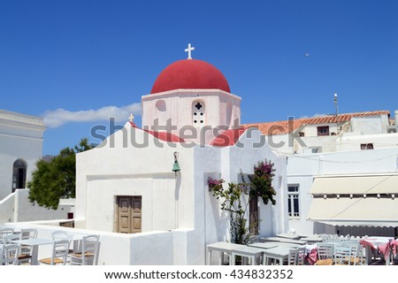 A white church with red roof and taverna tables on Mykonos island, Greece - stock photo