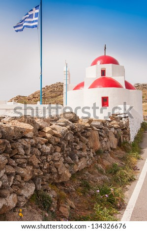 A white church with red roof and the Greek flag