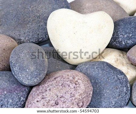 a White colored stone heart surrounded by other natural stones - stock photo