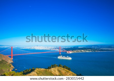 A white cruise ship passing under the Golden Gate Bridge in San Francisco, California, USA.  Daytime. - stock photo