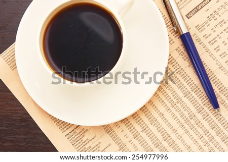 A white cup of coffee on paper table numbers - stock photo