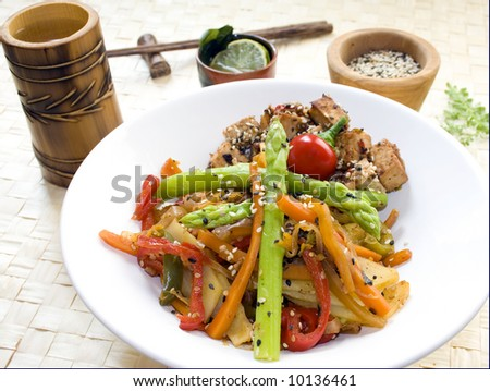 A white dish full of stir-fry mixed vegetables (red and green pepper, carrots, potatoes and asparagus) and tofu cubes, surrounded by a bamboo cup, chopsticks, lime and basil and white and black - stock photo