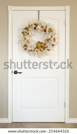 A white door with a white Christmas wreath with gold ornaments - stock photo