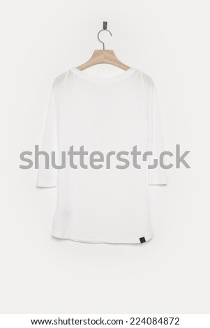 A white empty t-shirts front side with wooden hanger isolated white background. - stock photo