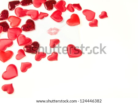 A white envelope sealed with a kiss on a white background with red scattered hearts and copy space. - stock photo