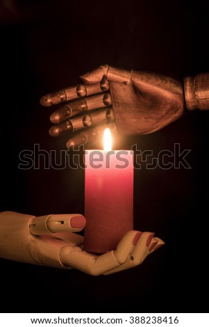 A white female hand holding a candle, a black man hand protects the flame