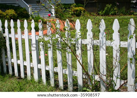 a white fence around a front yard