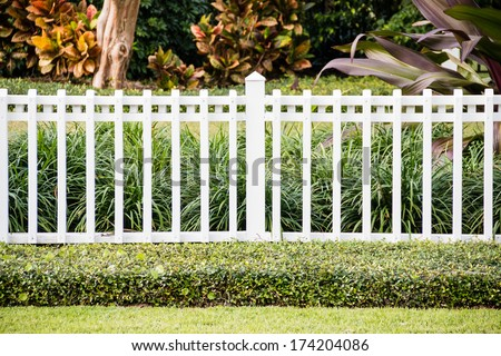 A white fence in front of a cozy and representative home with a very well-groomed green lawn - stock photo