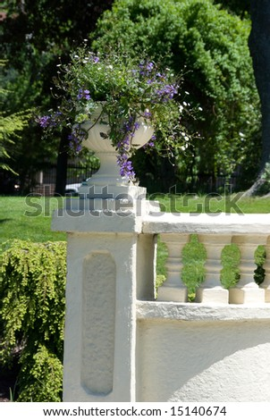 A white garden balustrade embellished by a potted plant,
