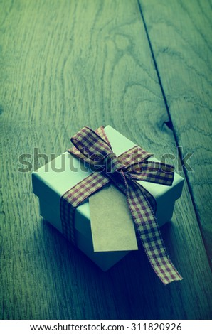 A white gift box with closed lid, tied to a bow with red and cream gingham ribbon.  Blank vintage label facing upwards. Cross processed for retro appearance. - stock photo