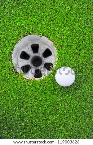 A white golf ball near the hole