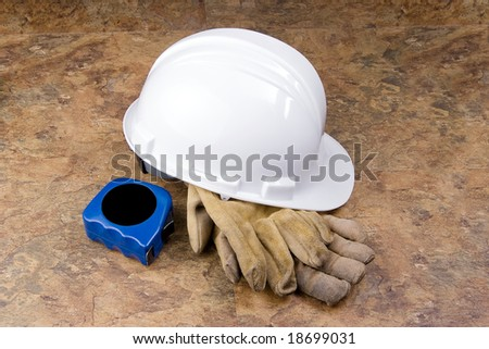 A white hard hat with well used work gloves and blue tape measure on a mottled background. - stock photo