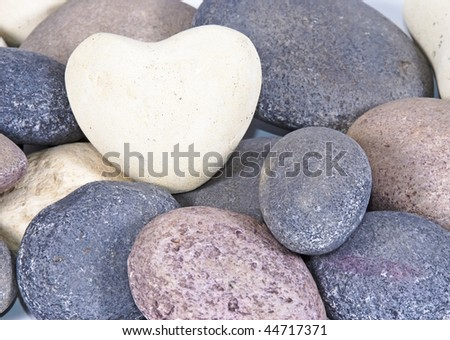 a White heart made of stone on natural colored stones - stock photo