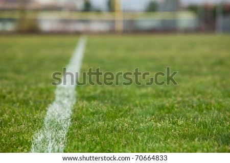 A White line on a soccer field with green grass - stock photo