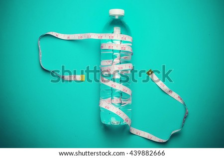 A  white measure tape wrapped around a bottle  of water  on blue background - stock photo