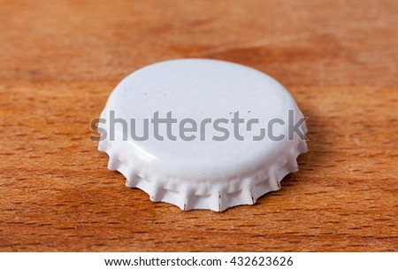 A white metal bottle cap on a wooden surface - stock photo