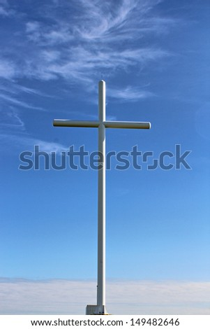 A white metal cross against a blue wispy sky